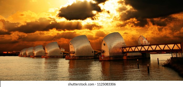 Thames Barrier, tidal protector, over dramatic sunset, commissioned by the Greater London Council, was complete by 1982, the world's second largest movable flood barrier.