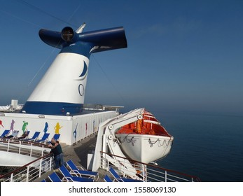 Thames Estuary, Essex, England - April 19th 2018:  Deep blue sea and sky seen from upper deck of cruise ship outbound to Northern Europe. Whale tail funnel and lifeboats.