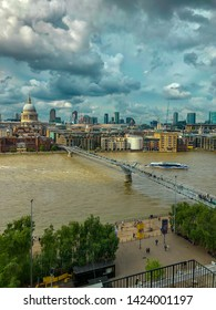 Thames river in London, UK 07/06/2019. Panoramic view of the river from the rooftop of Tate Modern Art Gallery. The river is crossed by Millennium Bridge. We can glimpse Saint Paul cathedral.