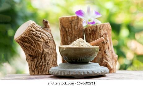 Thanaka or Hesperethusa crenulata, logs and powder on a natural background.