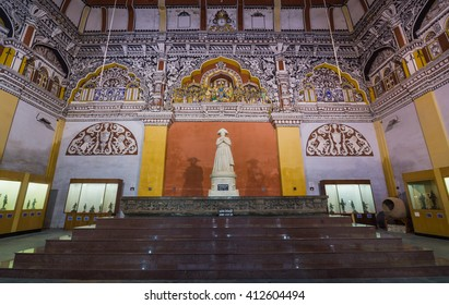 Thanjavur, India - October 14, 2013: The Durbar hall at Thanjavur Palace. High ceilings. Statue of Serfoji II. Scenery of Lord Rama and his Lanka conquest. White on red decorations of the wall.