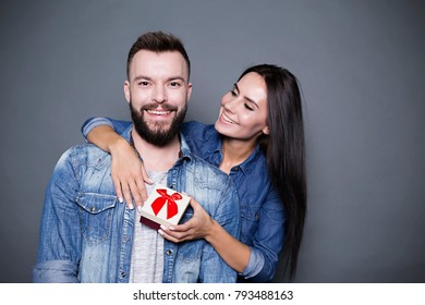 Thank you. Beautiful happy woman presents a gift to her beloved and hugs him from behind on a gray background. Valentine's Day.