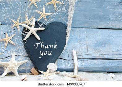 Vielen Dank für die schönen Ferien am Strand: Muschelhintergrund auf rustikalem blauem Holz. Auf der Tafel anzeigen verschiedene Muscheln und Sternschiffe mit weißem Sand und Fischnetz.