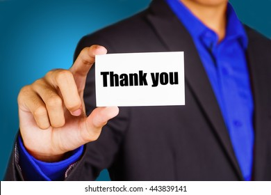 """""""Thank you"""" black and red text on white card hold by young business man wearing a business jacket - economic, finance and crisis concept"""