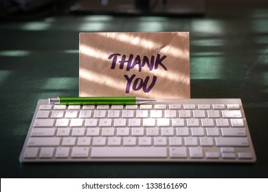 Thank you card inside a brown envelope left on the keyboard of an office table