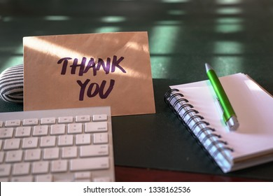 Thank you card inside a brown envelope left on an office table