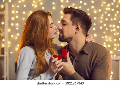 Thank you, darling. Young man giving jewelry to his girlfriend on romantic date. Happy couple in love kissing after she said yes and accepted marriage proposal and gold engagement ring