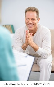 Thank you doctor. Pleasant handsome smiling senior man sitting on the couch and talking with psychologist while expressing positivity