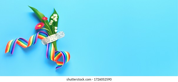 Thank you doctors and nurses! Rainbow ribbon and bouquet of red primrose and lily of the valley flowers attached with medical aid patch. Creative panoramic flat lay on blue mint background text space.