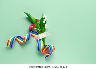 Thank you doctors and nurses! Rainbow ribbon and bouquet of red primrose and lily of the valley flowers attached with medical aid patch. Creative flat lay on mint green background, text space.