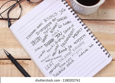 Thank you gratitude words letter in many languages, written on notepad, work desk top view. Motivational business typography quotes concept