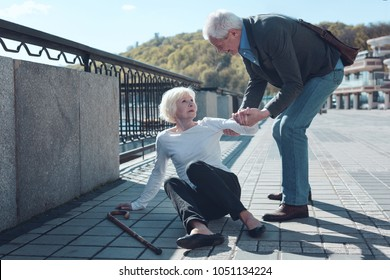 Thank you for helping me. Cheerful older male bypasser smiling while helping senior lady to stand up after falling to the ground during a daily walk.