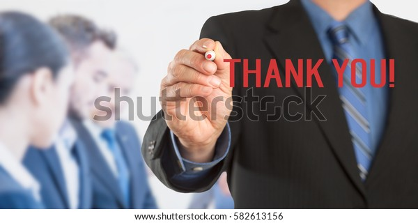 Thank You, Male hand in business wear holding a thick pen writing, with office team blurred in background, digital composing.