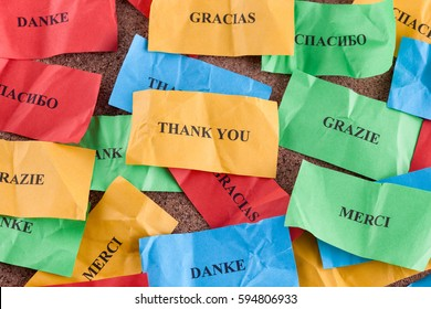 Thank you in many languages on colorful pieces of paper.