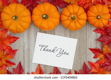 Thank You message with pumpkins and fall leaves leafs on weathered wood