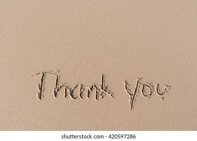 """""""Thank you"""" message written on sand beach"""