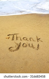 Thank you, a message written in the sand at the beach.