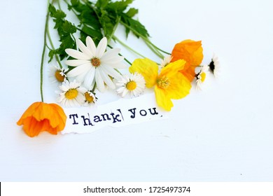 A thank you note with a bouquet of wild spring flowers . Welsh poppies and daisies on a white wooden background. A floral arrangement in yellow, orange and white suitable for a thank you card .