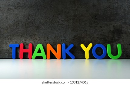 Thank you sign and word on colorful letters for thanks giving message to customers on dark grunge background with copy space.