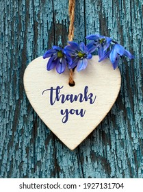 Thank You or thanks greeting card with spring flowers and decorative white heart on a blue wooden background.International Thank You Day or Mother's Day concept.