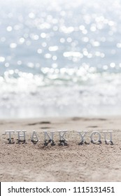 thank you words written on the sand of the beach