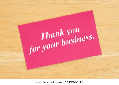 Thank you for your business text on pink card on wood desk
