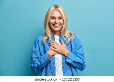 Thankful middle aged woman presses hands to chest smiles broadly and being touched to receive compliment dressed in fashionable clothes stands indoor against blue background. Body language concept