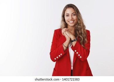 Thankful pleased young gorgeous european curly-haired woman, wearing red jacket pressing palms together grateful, appreciating cute romantic gesture, smiling receiving bday congratulations