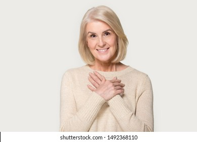 Thankful senior mature smiling woman isolated on grey studio background hold hands on chest feel appreciation and love, grateful pleased aged female look at camera thanking showing faith