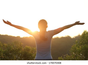 thankful woman open arms to the sunrise stand top of mountain