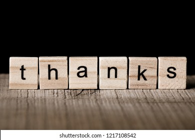 Thanks Blocks on the wooden desk with black background.