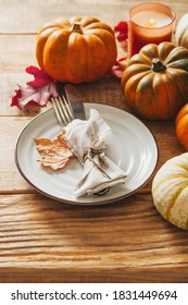 Thanks giving day serving table with plate, taleware, pumpkins and leaves on wooden background, copy space, top view, vertical