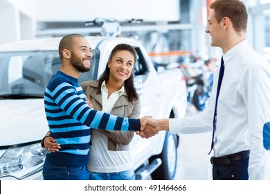 Thanks for the help. Portrait of a salesman shaking hands with a happy couple after selling them a new car at the dealership