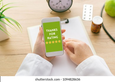 Thanks for rating message on smartphone screen in female doctor hand. Patients and customer service survey feedback concept.