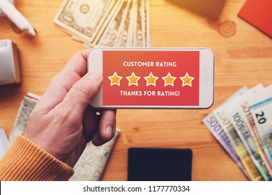 Thanks for rating message on smartphone screen in male hand. Customer service survey feedback concept.