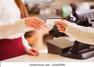 Thanks for your purchase. Cropped image of a customer paying to shop assistant by a credit card at the cash desk