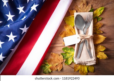 Thanksgiving autumn place setting with cutlery and arrangement of colorful fall leaves with american flag