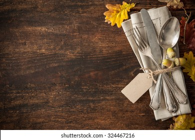 Thanksgiving autumn place setting with cutlery and arrangement of colorful fall leaves