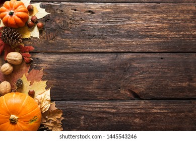 Thanksgiving or Autumnal holiday background, top view, copy space. Autumnal holiday composition with pumpkins, nuts, yellow leaves.