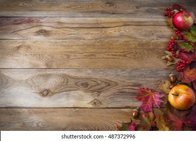 Thanksgiving background with apples, acorns, berries and fall leaves on the old wooden background. Thanksgiving background with seasonal berries and fruits. Abundant harvest concept.