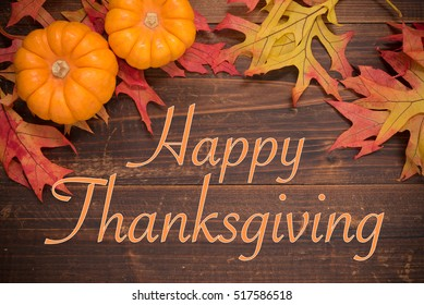 Thanksgiving background with Autumn oak leaves and pumpkins on a wooden background forming a border
