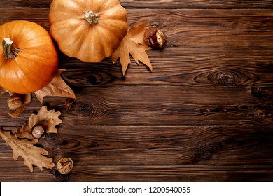 Thanksgiving background concept. Local produce pumpkin, chestnut, autumn dry oak & maple leaves and anise for decoration on wood textured table. Close up, copy space, top view, flat lay.