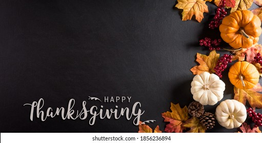 Thanksgiving background decoration from dry leaves,red berries and pumpkin on blackboard background. Flat lay, top view for Autumn, fall, Thanksgiving concept.