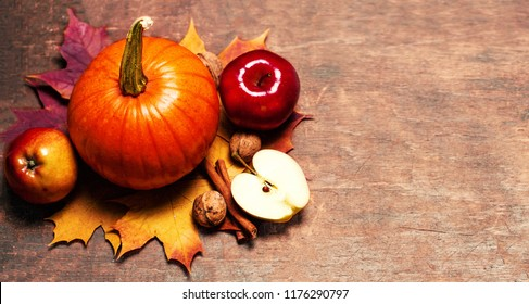 Thanksgiving Background with orange pumpkins, apples and yellow leaves on wooden table with copy space. Autumn Pumpkins. Flat lay