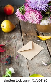 Thanksgiving background with seasonal fruits, flowers and craft paper envelope on a rustic wooden table. Autumn harvest concept. Confession in feelings. Selective focus, Space for text