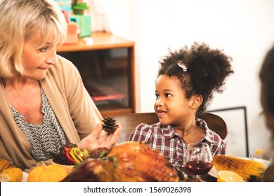 Thanksgiving Celebration Tradition Family Dinner Concept.family having holiday dinner and cutting turkey.Young black adult woman and her daughter happy.