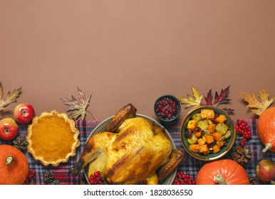 Thanksgiving charity dinner invitation template or mock-up with copy space for a greeting text, top down view on traditional festive food such as turkey, pumpkin pie, and cranberry sauce