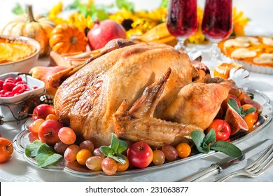 Thanksgiving or Christmas dinner. Roasted turkey on holiday table with pumpkins, flowers and wine