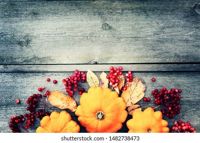 THANKSGIVING COMPOSITION ON RUSTIC WOODEN BACKGROUND WITH PUMPKINS,BERRIES AND LEAVES