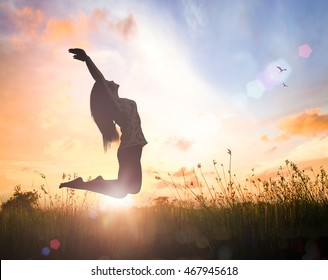 Thanksgiving concept: Silhouette of happy woman jumping with her hands raised at orange autumn nature sunset background